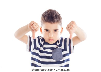 Portrait of a cute little boy giving thumbs down sign with sad expression