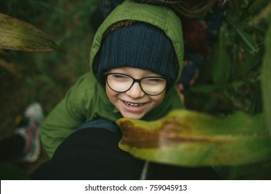 Portrait of cute little boy in glasses in the cornfield smiling