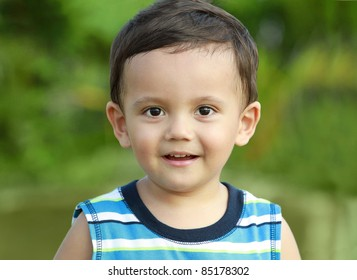 portrait of cute little boy in green nature