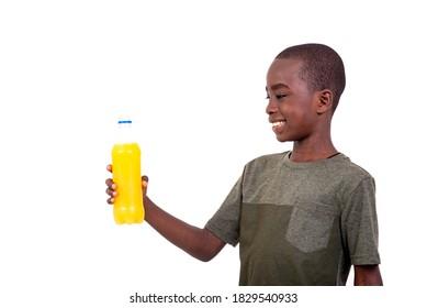 portrait of a cute little boy holding a plastic bottle of orange juice smiling.
