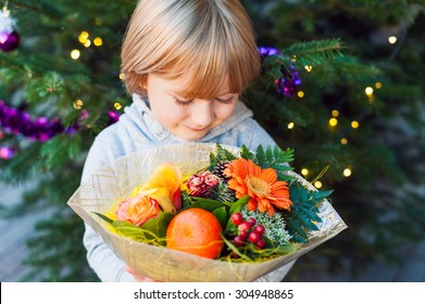Portrait of a cute little boy holding christmas flower bouquet, standing next to christmas tree