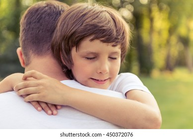 Portrait of cute little boy hugging his father while resting outdoors