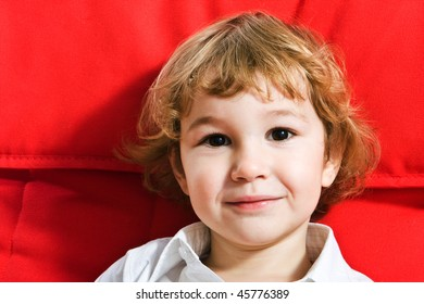 Portrait of cute little boy on red background