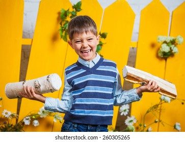 Portrait of a cute little boy with pile of firewood at yellow fence background