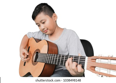 Portrait of a cute little boy playing acoustic guitar in the studio, isolated on white background
