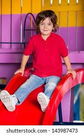 Portrait of cute little boy playing on slide in kindergarten