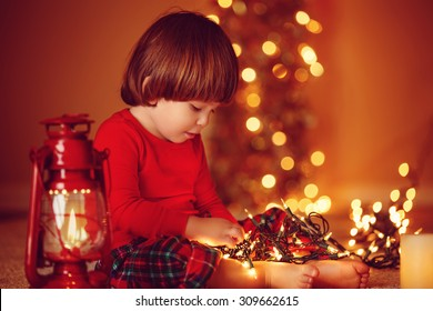 Portrait of cute little boy playing with Christmas light at home, with copy space