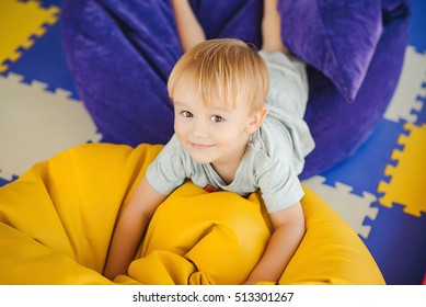 Portrait of a cute little boy playing on the playground in kindergarten.