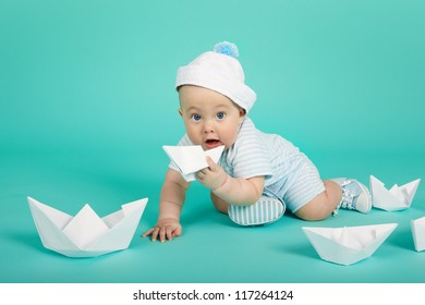 Portrait of cute little boy plays with toy ship. Sea theme