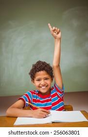 Portrait of cute little boy raising hand in classroom