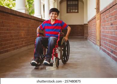 Portrait of cute little boy sitting in wheelchair in school corridor