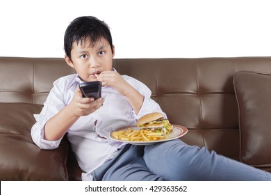 Portrait of a cute little boy sitting on the sofa while watching tv and enjoying a plate of fast food
