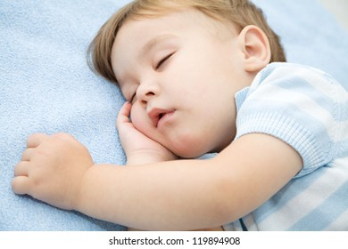 Portrait of a cute little boy sleeping on white pillow