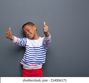 Portrait of a cute little boy smiling with thumbs up sign on gray background