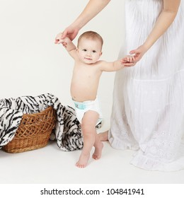 Portrait of cute little boy stand with mother help over white