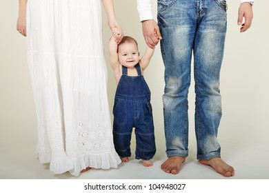 Portrait of cute little boy stand with mother and father help