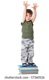 Portrait of a cute little boy standing on books. Isolated over white background.
