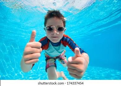 Portrait of a cute little boy swimming underwater