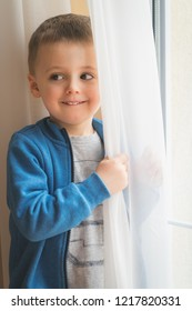 Portrait of a cute little Caucasian boy hiding behind a curtain next to the window