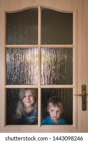 Portrait of a cute little Caucasian boy and girl hiding behind a door with glass windows while playing hide and seek