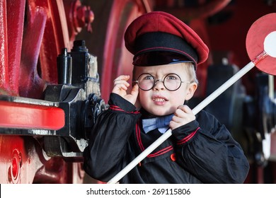 Portrait of a cute little child boy with annoyed facial expression as nostalgic railroad conductor and metal-rimmed glasses, cap and signaling disk/Upset Little Railroad Conductor