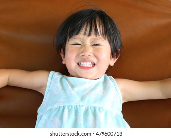 Portrait of cute little child girl lying on sofa with smile