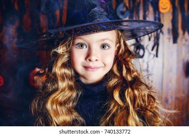 Portrait of a cute little child girl in a witch costume with magic wand. Happy Halloween!
