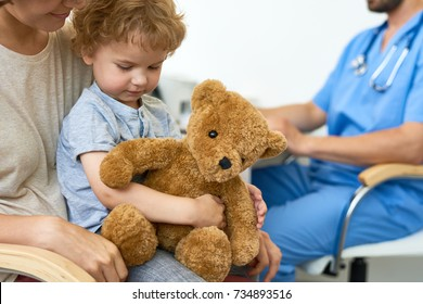 Portrait of cute little child sitting on mothers lap in doctors office waiting for check up hugging plush teddy bear toy