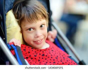 Portrait of a cute little disabled girl in a wheelchair. Child cerebral palsy. Inclusion. Family with disabled kid.