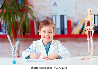 portrait of cute little doctor writing notes in lab