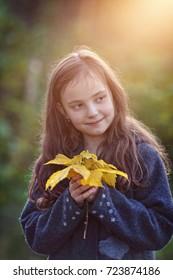 Portrait of a cute little girl in an autumn day