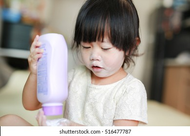 Portrait of cute little girl with baby powder on her face. Little girl pour the talcum to the hand.