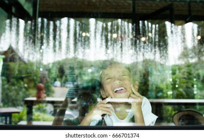 Portrait of cute little Girl Behind Glass with