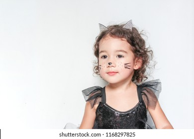 Portrait of a cute little girl in black Halloween costume party. Face painting as  a cat isolated.
