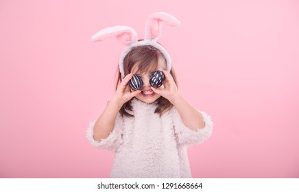 Portrait of a cute little girl with Bunny ears and Easter eggs, isolated on pink background