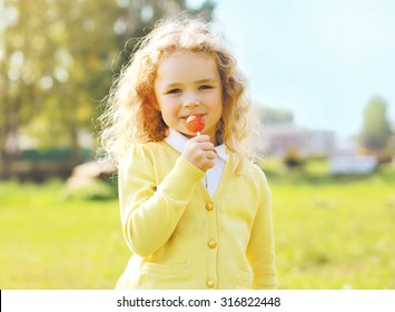 Portrait cute little girl child with caramel on stick