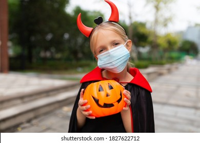 Portrait of cute Little Girl in costume of evil at home. Happy Halloween during coronavirus covid-19 pandemic quarantine concept. Kid wearing medical mask