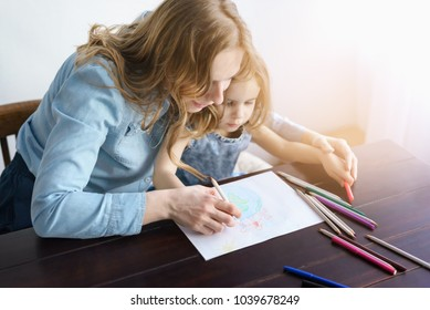 Portrait of cute little girl creating art on paper with colored pencils. Mom with excitement and smile helps her daughter in the process of drawing. Concept of education.