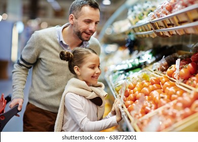 Portrait of cute little girl with dad leaning over vegetable counter choosing fresh ripe tomatoes and other vegetables in supermarket