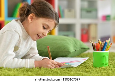 Portrait of cute little girl drawing at home