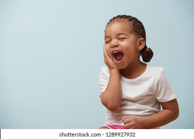 Portrait of cute little girl dressed for sport. She sits and yawns from tiredness. Pale blue background.