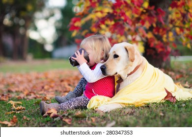 A portrait of a cute little girl drinking tea from a mug and sitting next to her dog, a yellow labrador wrapped up in a warm blanket