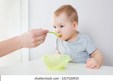 portrait of cute little girl eating from plastic spoon