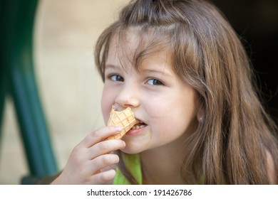 Portrait of cute little girl eating ice cream.