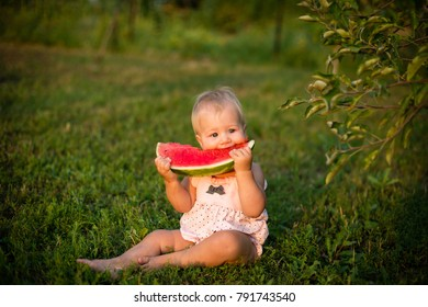 Portrait of a cute little girl eating watermelon