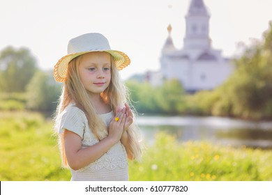 Portrait of a cute little girl in a hat on a background of a church on a summer day