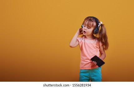 Portrait of cute little girl in headphones and with phone in the studio against yellow background.