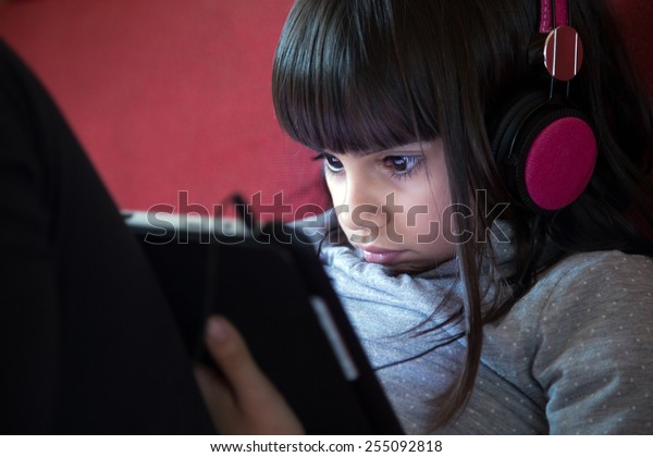 Portrait of a cute little girl with headphones using a tablet pc at home