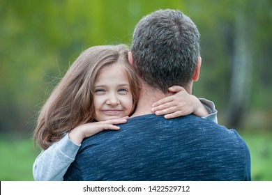Portrait of cute little girl held in father's arms. Happy loving family. Father and his daughter child girl playing hugging. Cute baby and daddy. Concept of Father day. Family holiday and togetherness