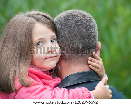 fda77ae4 Portrait of cute little girl held in father's arms. Happy loving family.  Father and